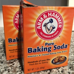 Two boxes of baking soda sit on a counter.